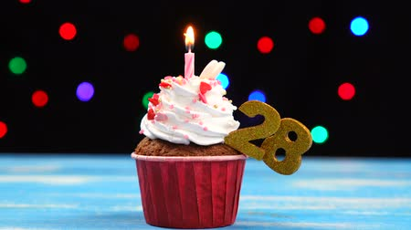 окропляет : Delicious birthday cupcake with burning candle and number 28 on multicolored blurred lights background