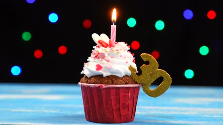 otuzlu yıllar : Delicious birthday cupcake with burning candle and number 30 on multicolored blurred lights background