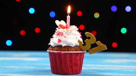 otuzlu yıllar : Delicious birthday cupcake with burning candle and number 31 on multicolored blurred lights background