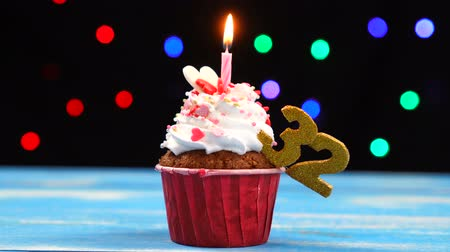 otuzlu yıllar : Delicious birthday cupcake with burning candle and number 32 on multicolored blurred lights background Stok Video