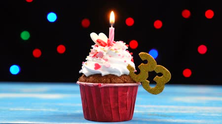 açoitado : Delicious birthday cupcake with burning candle and number 33 on multicolored blurred lights background