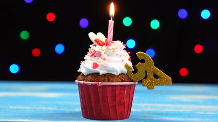otuzlu yıllar : Delicious birthday cupcake with burning candle and number 34 on multicolored blurred lights background Stok Video