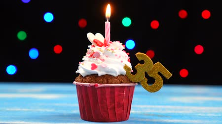 otuzlu yıllar : Delicious birthday cupcake with burning candle and number 35 on multicolored blurred lights background