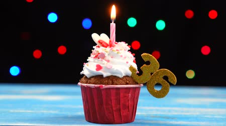 otuzlu yıllar : Delicious birthday cupcake with burning candle and number 36 on multicolored blurred lights background