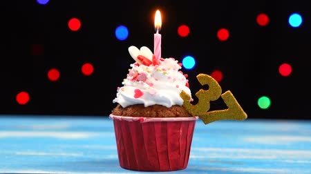 otuzlu yıllar : Delicious birthday cupcake with burning candle and number 37 on multicolored blurred lights background Stok Video