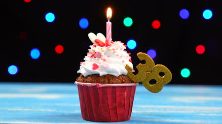 otuzlu yıllar : Delicious birthday cupcake with burning candle and number 38 on multicolored blurred lights background
