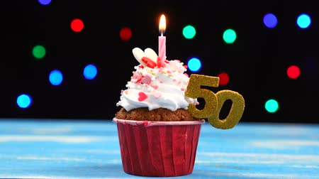 šlehačka : Delicious birthday cupcake with burning candle and number 50 on multicolored blurred lights background
