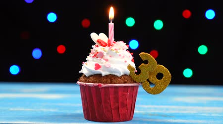 otuzlu yıllar : Delicious birthday cupcake with burning candle and number 39 on multicolored blurred lights background Stok Video
