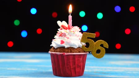 seis : Delicious birthday cupcake with burning candle and number 56 on multicolored blurred lights background