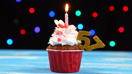 sete : Delicious birthday cupcake with burning candle and number 57 on multicolored blurred lights background