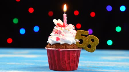 acht : Delicious birthday cupcake with burning candle and number 58 on multicolored blurred lights background