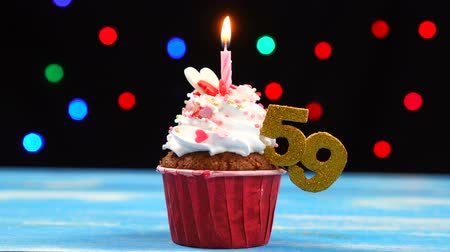 devět : Delicious birthday cupcake with burning candle and number 59 on multicolored blurred lights background