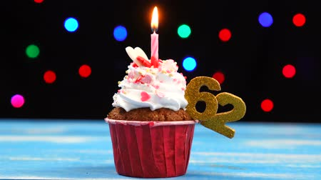 šlehačka : Delicious birthday cupcake with burning candle and number 62 on multicolored blurred lights background