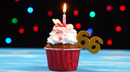 seis : Delicious birthday cupcake with burning candle and number 66 on multicolored blurred lights background Vídeos