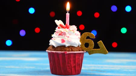 sete : Delicious birthday cupcake with burning candle and number 67 on multicolored blurred lights background