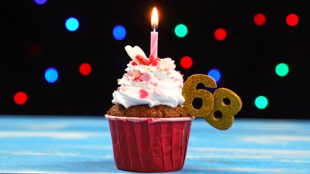acht : Delicious birthday cupcake with burning candle and number 68 on multicolored blurred lights background