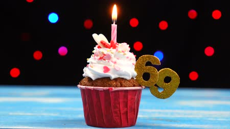 gênero alimentício : Delicious birthday cupcake with burning candle and number 69 on multicolored blurred lights background