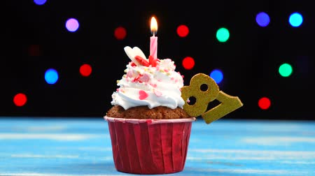 ochenta : Delicious birthday cupcake with burning candle and number 81 on multicolored blurred lights background