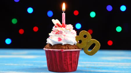 gênero alimentício : Delicious birthday cupcake with burning candle and number 80 on multicolored blurred lights background