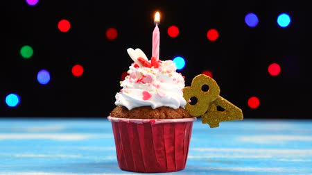 ochenta : Delicious birthday cupcake with burning candle and number 84 on multicolored blurred lights background Archivo de Video