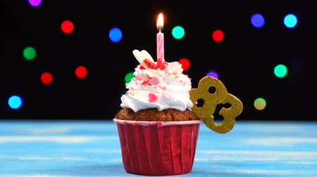 ochenta : Delicious birthday cupcake with burning candle and number 83 on multicolored blurred lights background