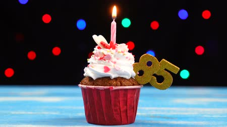 ochenta : Delicious birthday cupcake with burning candle and number 85 on multicolored blurred lights background