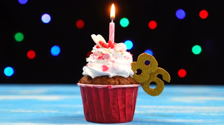 seis : Delicious birthday cupcake with burning candle and number 86 on multicolored blurred lights background