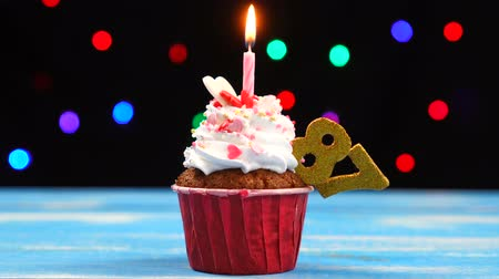 ochenta : Delicious birthday cupcake with burning candle and number 87 on multicolored blurred lights background
