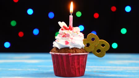 окропляет : Delicious birthday cupcake with burning candle and number 88 on multicolored blurred lights background