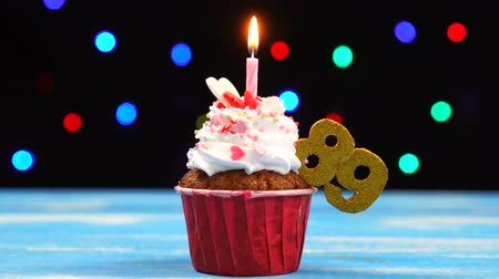 ochentas : Delicious birthday cupcake with burning candle and number 89 on multicolored blurred lights background