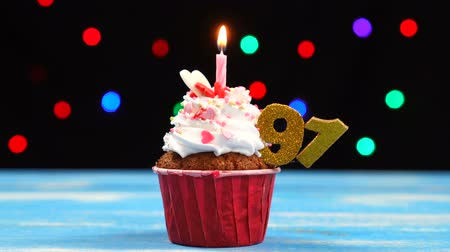 šlehačka : Delicious birthday cupcake with burning candle and number 91 on multicolored blurred lights background Dostupné videozáznamy