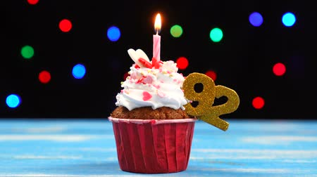 šlehačka : Delicious birthday cupcake with burning candle and number 92 on multicolored blurred lights background