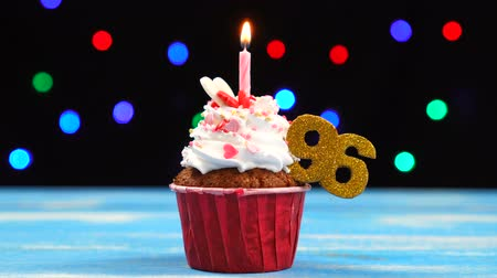 seis : Delicious birthday cupcake with burning candle and number 96 on multicolored blurred lights background