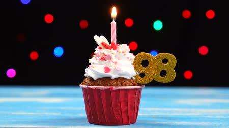 acht : Delicious birthday cupcake with burning candle and number 98 on multicolored blurred lights background