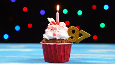 sete : Delicious birthday cupcake with burning candle and number 97 on multicolored blurred lights background