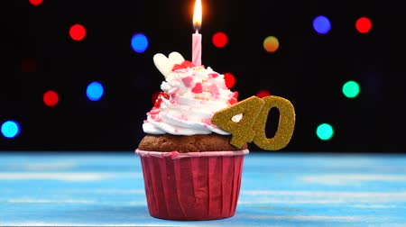 čtyřicet : Delicious birthday cupcake with burning candle and number 40 on multicolored blurred lights background