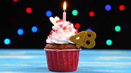 čtyřicet : Delicious birthday cupcake with burning candle and number 48 on multicolored blurred lights background