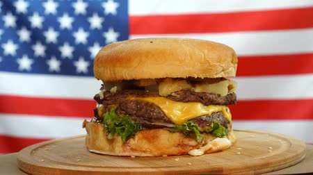 bacon burger : Fresh juicy burger with cheese, sauce and vegetables rotating on a wooden board on us flag background.