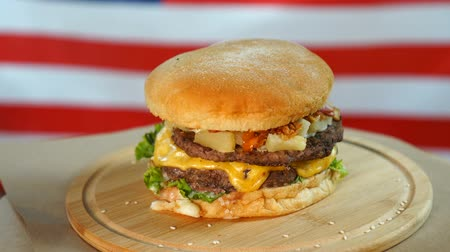 bacon burger : Fresh juicy burger with cheese, sauce and vegetables rotating on a wooden board in front of American Flag