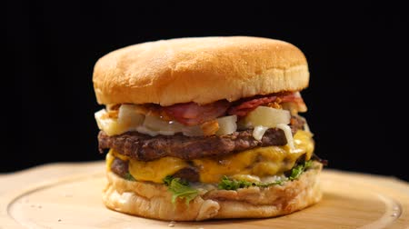 bacon burger : Beef juicy burger is fast rotating on the table on a black background.