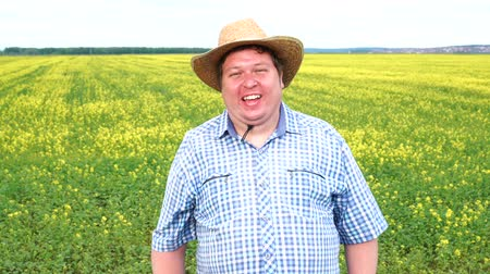 ekili : Portrait of happy farmer who stands and laughs in the field on a sunny day