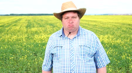 elutasít : Farmer standing in field and shaking his head, says no, in the field on a sunny day