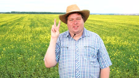 victory day : Farmer standing in field and showing sign of victory, wear cowboy hat on a sunny day Stock Footage