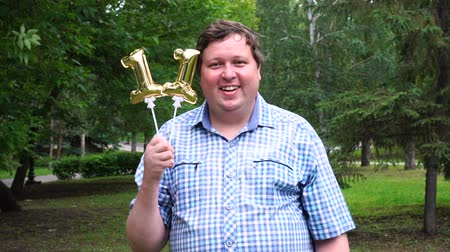 eleven people : Big man holding golden balloons making the 11 number outdoor. 11th anniversary celebration party Stock Footage