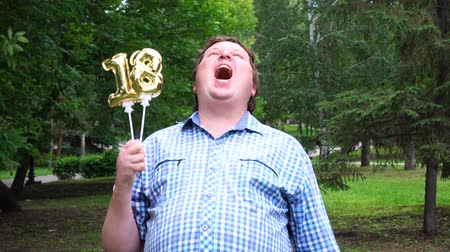 eighteen : Big man holding golden balloons making the 18 number outdoor. 18th anniversary celebration party Stock Footage