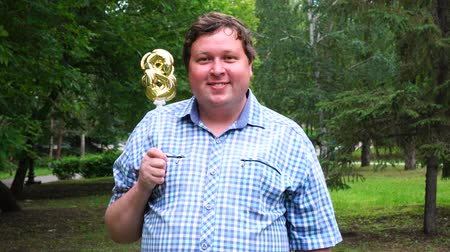 osm : Big man holding golden balloon making the 8 number outdoor. 8th anniversary celebration party