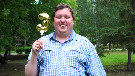 felicitação : Big man holding golden balloon making the 3 number outdoor. 3th anniversary celebration party Stock Footage