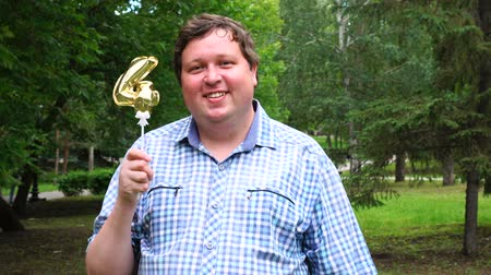 felicitação : Big man holding golden balloon making the 4 number outdoor. 4th anniversary celebration party Stock Footage