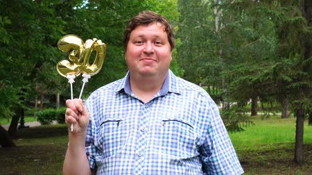 otuzlu yıllar : Big man holding golden balloons making the 30 number outdoor. 30th anniversary celebration party