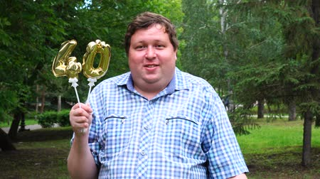 felicitação : Big man holding golden balloons making the 40 number outdoor. 40th anniversary celebration party